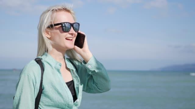 stockvideo's en b-roll-footage met mooie slanke vrouw met lang blond haar en groene shirt staan en praten over de telefoon over zee van de achtergrond - blond curly hair