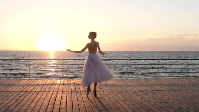 schöne zeitlupe szene der jungen ballerina wirbeln auf einen holzboden im freien in zeitlupe. meer, sonne scheint vor dem hintergrund - ballettschuh stock-videos und b-roll-filmmaterial