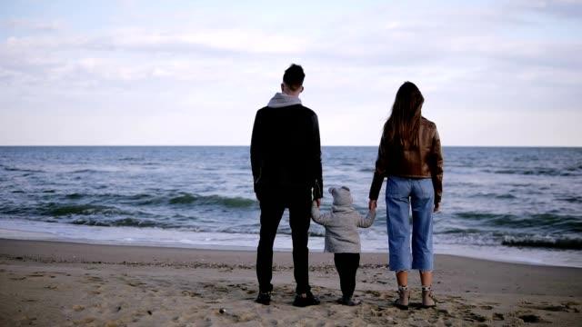 海の前に立って地平線を見つめている子供を持つ若い、流行のカップルの美しい、スローモーションシーン。風が強く、寒い天気 - 息子点の映像素材/bロール