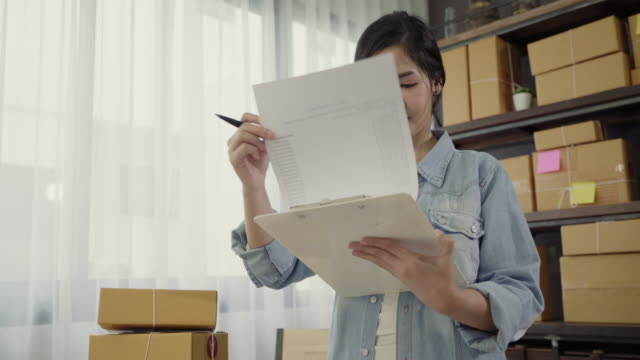 beautiful smart asian young entrepreneur business woman owner of sme checking product on stock and write on clipboard working at home. small business owner at home office concept. - owner laptop smartphone video stock e b–roll