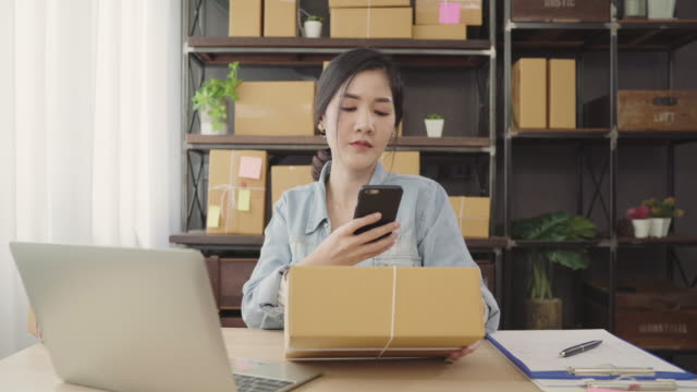 beautiful smart asian young entrepreneur business woman owner of sme checking product on stock scan qr code working at home. small business owner at home office concept. - owner laptop smartphone video stock e b–roll