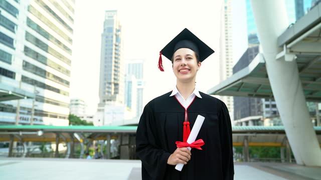 美麗的笑臉畢業的學生女孩年輕女子走在帽袍步行和持有文憑卷軸。 - 文憑 個影片檔及 b 捲影像