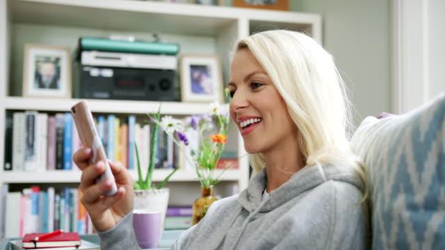 stockvideo's en b-roll-footage met mooie lachende blonde vrouw op thuis via mobiele telefoon - bewondering