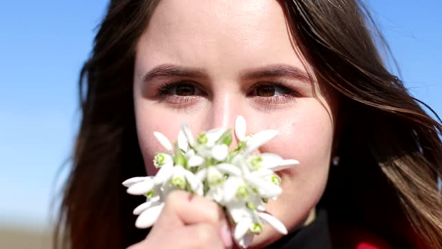Beautiful smiling brunette girl holding bouquet of snowdrops first spring flowers
