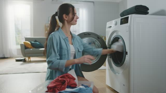 stockvideo's en b-roll-footage met mooie lachende brunette jonge vrouw zit voor een wasmachine in huiselijke jeans kleding. ze laadt de wasmachine met vuile was. lichte en ruime woonkamer met modern interieur. - vrouw schoonmaken