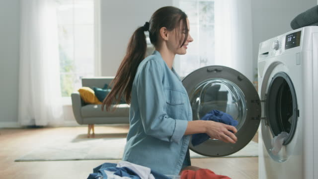 beautiful smiling brunette young woman sits in front of a washing machine in homely jeans clothes. she is dancing and loading the washer with dirty laundry. bright and spacious living room with modern interior. - pranie filmów i materiałów b-roll