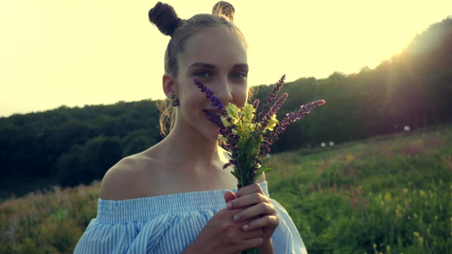 beautiful smiling girl standing in a countryside with a bouquet of field flowers in hands at golden sunset video