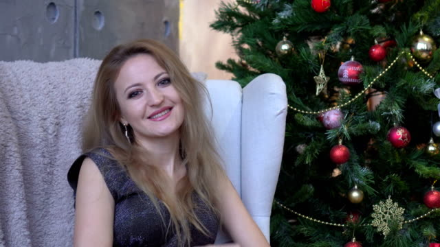 A beautiful smiling woman in a shiny dress waving and sitting on a chair near a christmas tree video
