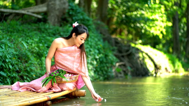 Beautiful Smiling Woman Spread Pink Flower Into The River