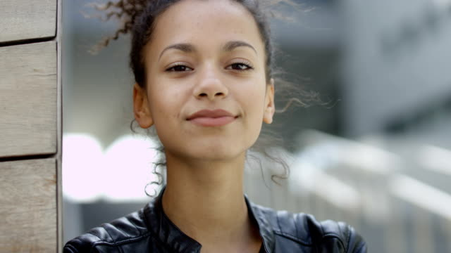 Beautiful smiling young woman in urban background looking to a camera. video
