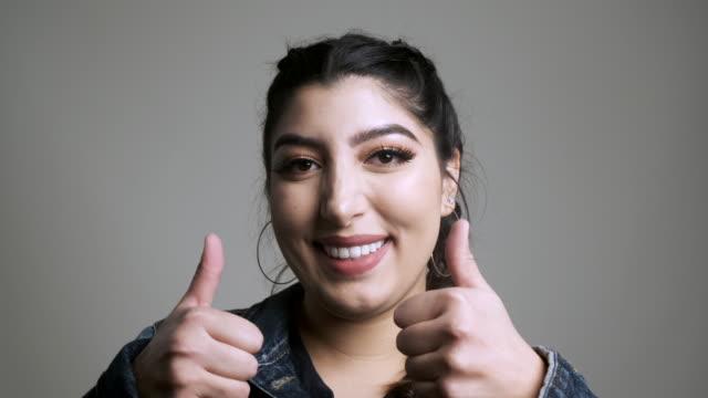vídeos de stock e filmes b-roll de beautiful smiling young woman looking at the camera - cabelo preto