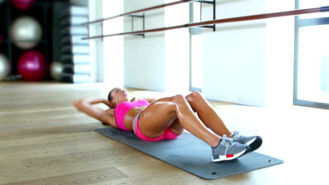 Beautiful sport woman doing press fitness exercise at sport gym video