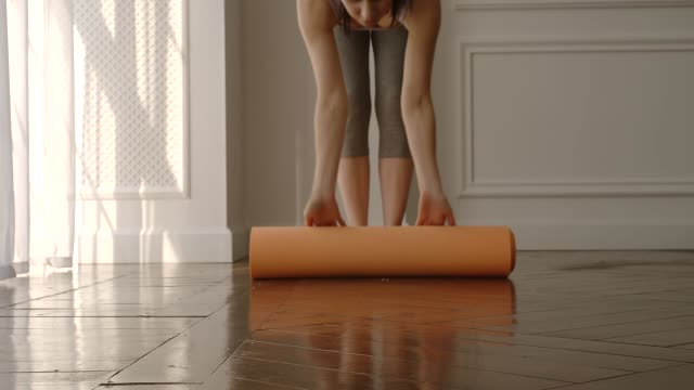 real time: beautiful sport woman opens a mat getting started for doing yoga at home - edificio residenziale video stock e b–roll