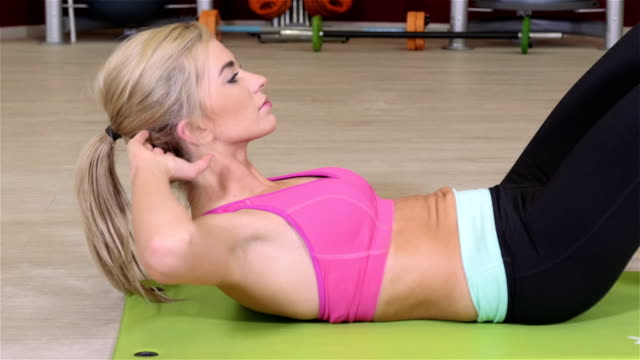 Beautiful sporty woman doing crunches on the floor in a fitness center.