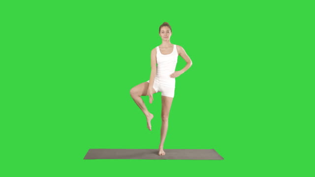 Beautiful sporty young woman in white sportswear working out idoing Utthita Hasta Padangustasana, Extended Hand to Big Toe pose on a Green Screen, Chroma Key