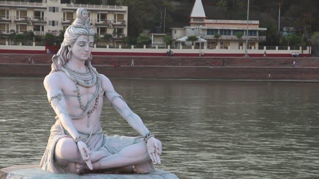 vacker staty av lord shiva på flodstranden av ganga river i rishikesh. - india statue bildbanksvideor och videomaterial från bakom kulisserna