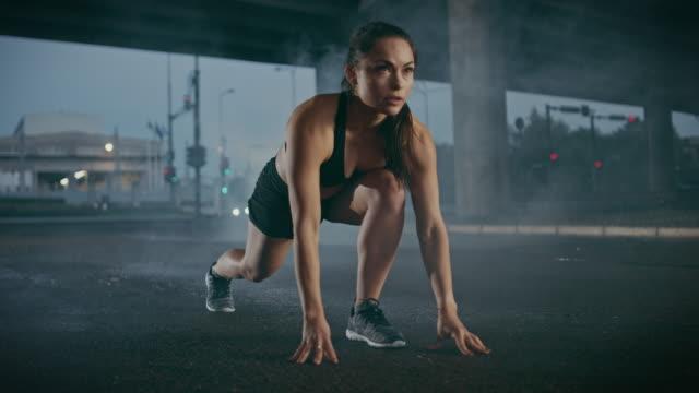 güzel güçlü fitness kız siyah spor top ve şort sprint başlar. bridge'de bir kentsel çevre altında bir otomobil içinde belgili tanımlık geçmiş ile çalışıyor. - başlama çizgisi stok videoları ve detay görüntü çekimi
