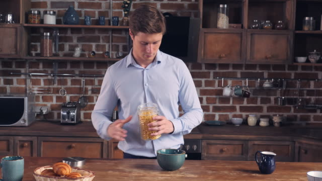 Beautiful student pouring cornflakes in bowl. video