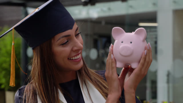 beautiful student wearing a graduation cap and gown holding a pink piggy bank looking at camera smiling - risparmi video stock e b–roll