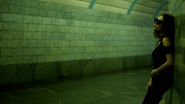 beautiful stylish girl in glasses stands in a pedestrian underpass near the wall