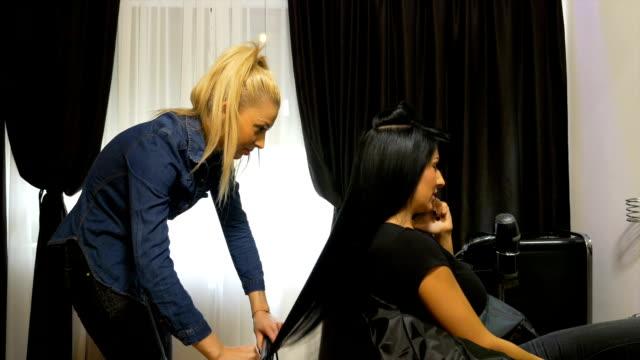 vidéos et rushes de belle femme élégante, obtenant son coiffeur au salon de beauté tout en parlant au téléphone mobile - coiffure
