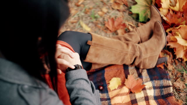 Beautiful, stylish, young womam uses smart clock sitting on plaid in autumn park. FullHD