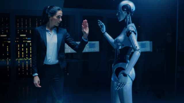 vídeos de stock e filmes b-roll de beautiful successful business woman wearing suit touching hands with humanoid robot activating collaboration, teamwork protocol. people and artificial intelligence working together - business woman hologram