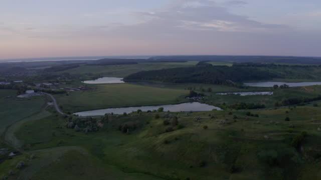 stockvideo's en b-roll-footage met mooie zomerzonsondergang met meren en groene heuvels - natuurgrond