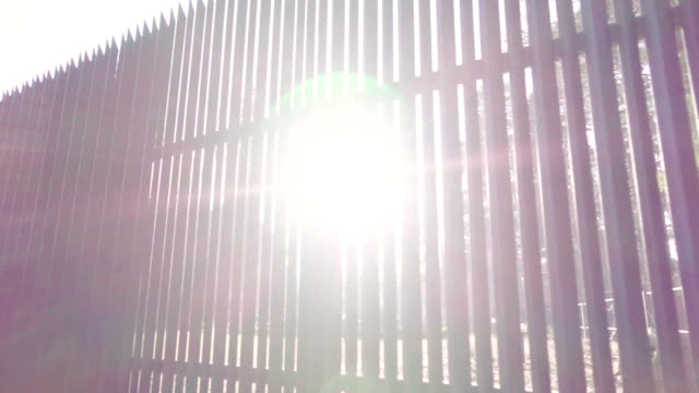 Beautiful sunlight through the fence video