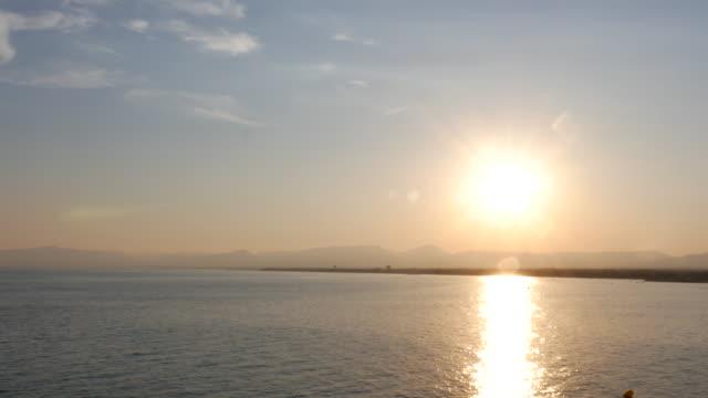 vídeos de stock e filmes b-roll de beautiful sunrise on a calm mediterranean beach - linha do horizonte sobre água