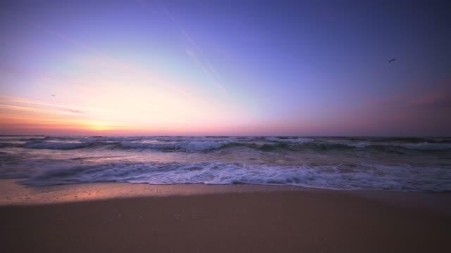 Beautiful sunrise over the beach and sea waves