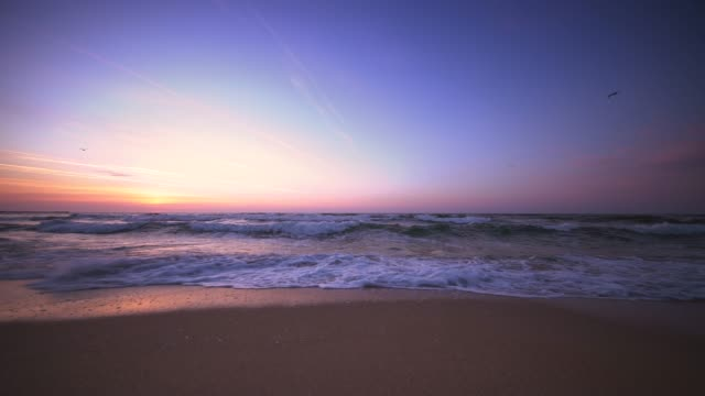beautiful sunrise over the beach and sea waves - sunset stock videos & royalty-free footage