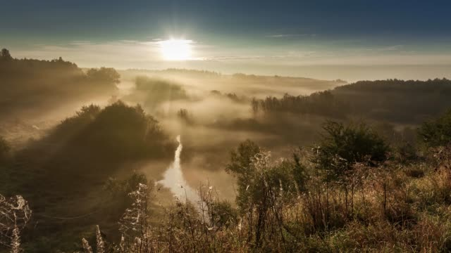 Beautiful sunrise over valley with stunning mist in autumn, timelapse, 4K