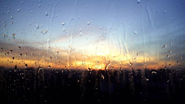 stockvideo's en b-roll-footage met prachtige zonsopgang terwijl het regent. kijken naar de zonsopgang achter het venster. 4k - regen zon