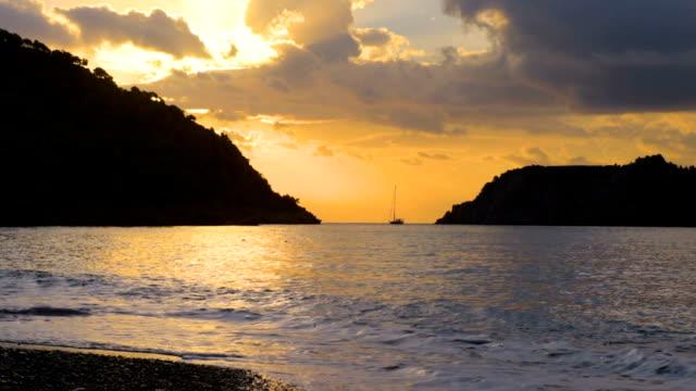 Beautiful sunset at beach, light beam Turkish seascape, Marmaris, Turkey Beautiful sunset at beach, amazing colors, light beam and boat. Turkish seascape, Marmaris, Turkey aegean turkey stock videos & royalty-free footage