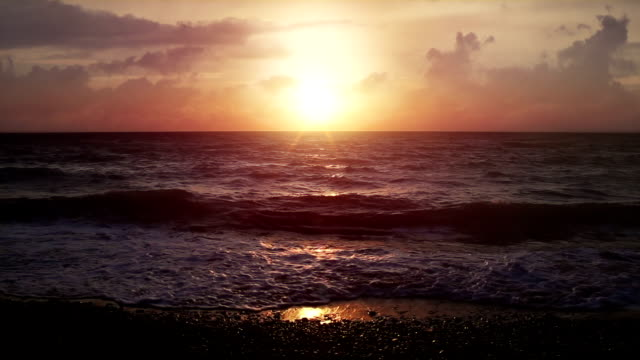 Beautiful sunset at the beach in slowmotion video