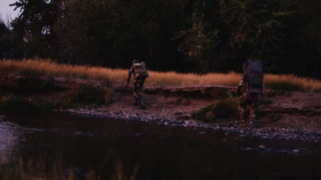 A beautiful sunset dances off the river as two hunters quickly stalk an animal just after dark in light. video