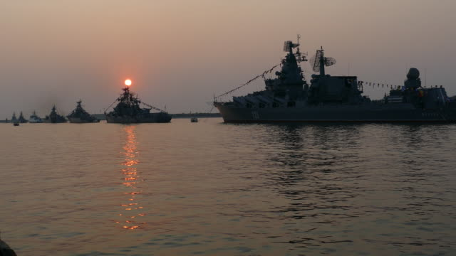 beautiful sunset in a bay with silhouettes of warships video