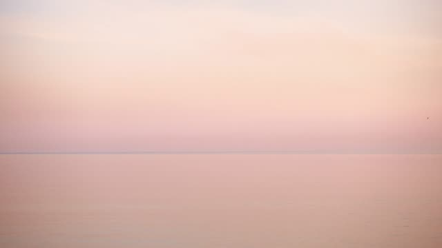 Beautiful sunset in pastel tones over calm water. Beautiful sunset in pastel tones over calm water, uhd. salt flat stock videos & royalty-free footage