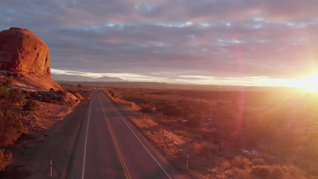 Beautiful Sunset Of Wilson Arch, Near Moab, Utah, With Semi Trucks Driving The Major Truck Route Delivering Freight