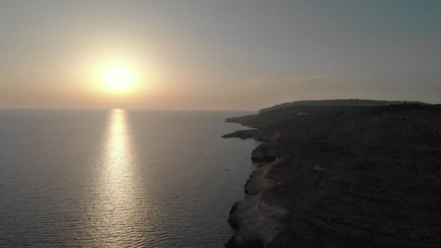 beautiful sunset over brilliant sea water with rocky shore, drone view