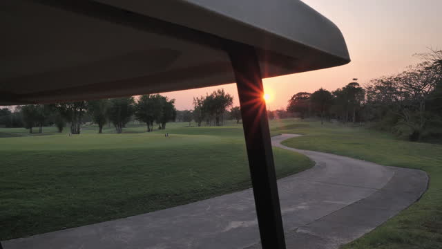 Beautiful sunset overlooking gold course.Golf car on the golf course,Golf course in the countryside,Green golf field, Golfing Holidays.Sports Cinemagraphs.Golf Concepts