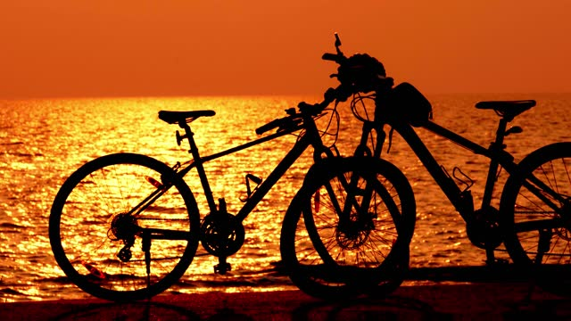 beautiful sunset view behind mtb, mountain bike, bicycle silhouette near ocean and beach with helmet for exercise outside in nature sunset time beautiful sunset view behind mtb, mountain bike, bicycle silhouette near ocean and beach with helmet for exercise outside in nature sunset time with wave and sea view coastal feature stock videos & royalty-free footage