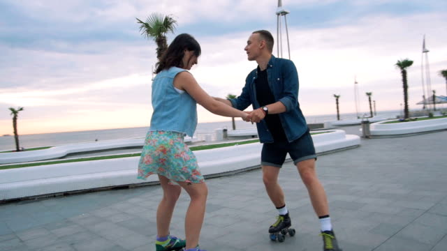 beautiful sweet couple riding on roller skates quads holding hands near the sea, slow motion - lama oggetto creato dall'uomo video stock e b–roll