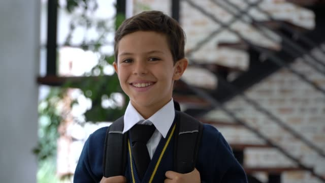 beautiful sweet little boy in school uniform carrying his backpack and smiling at camera - scolaro video stock e b–roll
