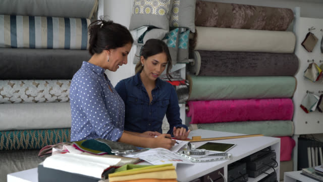 Beautiful team of interior designers working on a design using a tablet and fabric swatches while talking Beautiful team of interior designers working on a design using a tablet and fabric swatches while talking looking very focused interior designer stock videos & royalty-free footage