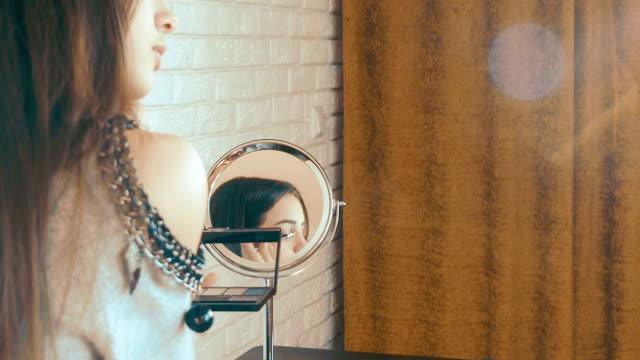 Beautiful teen girl doing makeup Beautiful teen girl doing makeup. mascara stock videos & royalty-free footage