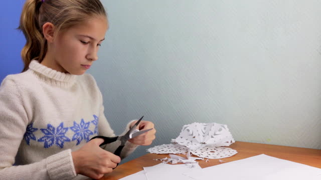 Beautiful teen girl painstakingly carves a snowflake out of paper video