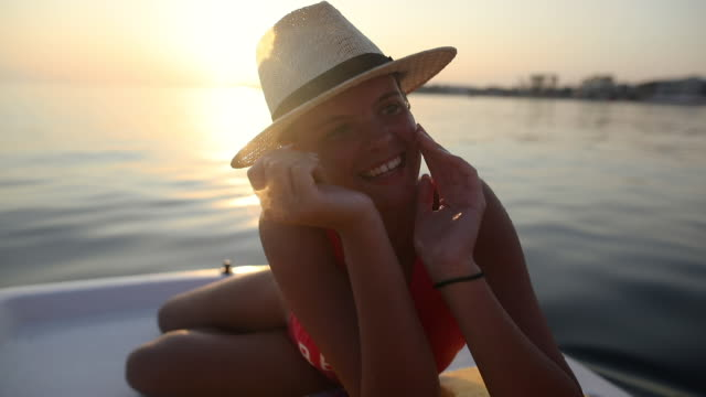 Beautiful Teenage Girl Relaxing and smiling on Pedal Boat with Sun Hat on