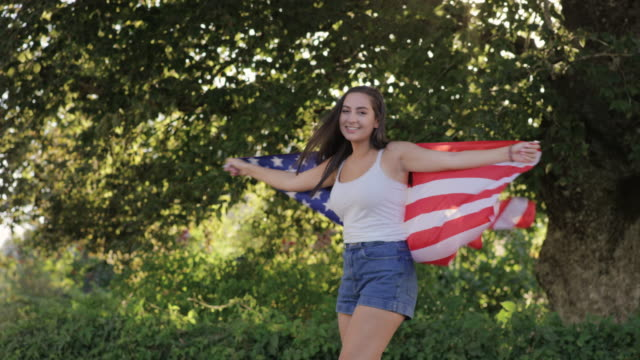 Beautiful teenage girl spinning around laughing with American Flag video